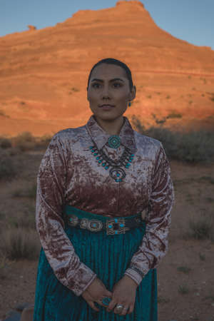 Navajo Woman standing in front of Rock Formation in the Arizona Desert