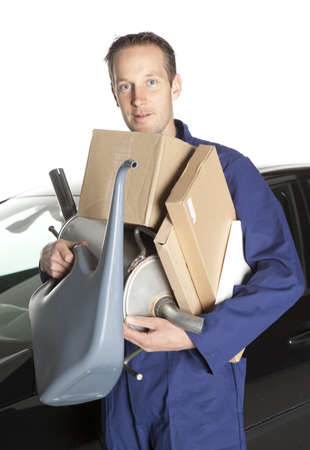 Mechanic looking at camera in studio with car