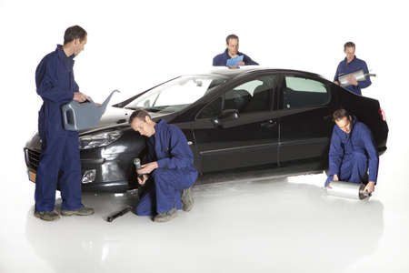 service car: Portrait of confident worker with handful of mechanic stuff in front of car over white background