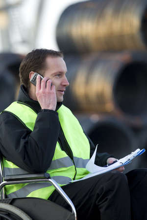 Physically challenged supervisor on call with notepad at industrial site