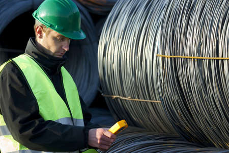 Handsome supervisor looking at geiger counter with cable wire rolls at construction site