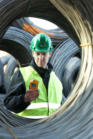 Supervisor inspecting while looking at geiger counter with cable wires at the site