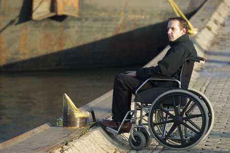 physical impairment: Relaxed disabled man spending some time alone on wheelchair outdoors Stock Photo