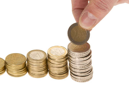 Man placing more coins on the stack isolated on white background