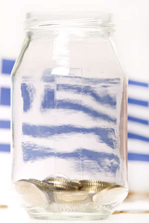 Euro coins in a jar with Greek flag in background Stock Photo