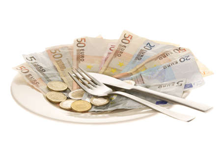 Plate full of euro notes and coins with fork and knife isolated on white background
