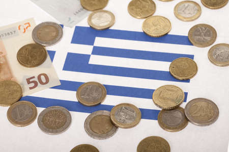 Few euro coins and paper currency on Greek flag indicating recession