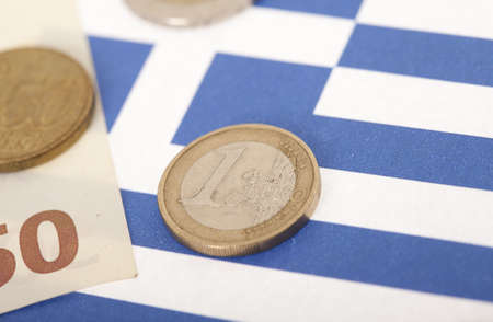 greek coins: Closeup of one euro coin on Greek flag Stock Photo