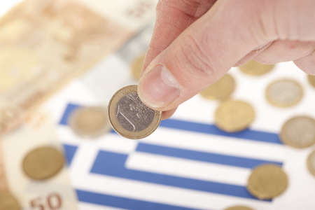 greek coins: Man investing euro coin to the national economy