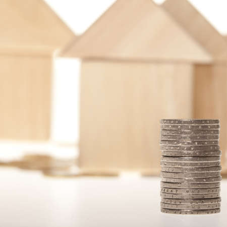 Stack of coins with residential structure isolated on white background Stock Photo
