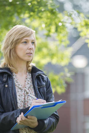 Serious woman with folder and pen outdoors Stock Photo - 15451083