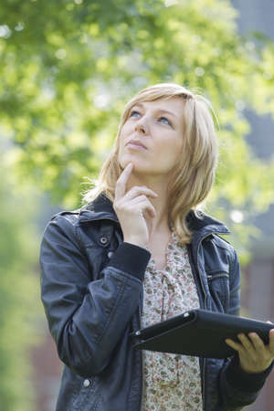 Thoughtful woman with digital tablet looking up Stock Photo - 15451080