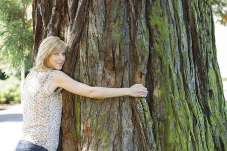 Young woman hugging large tree trunk Standard-Bild