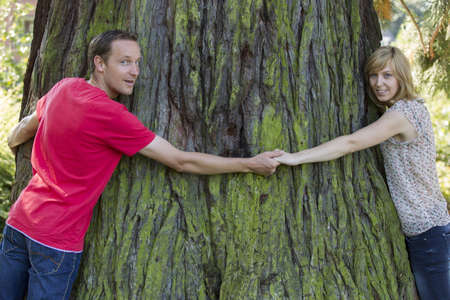 looking around: Couple holding hands and hugging large tree trunk Stock Photo