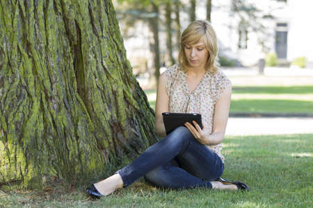 Woman using digital tablet by tree on lawn photo