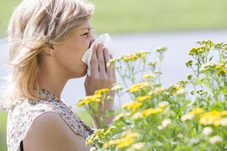 estornudo: Mujer que sopla la nariz en el tejido delante de las flores Foto de archivo