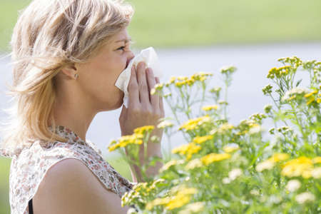 Woman blowing nose into tissue in front of flowers photo