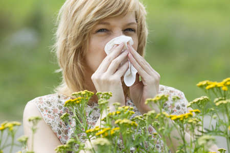 Woman blowing nose into tissue outdoors photo