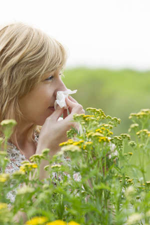Woman blowing nose into tissue outdoors