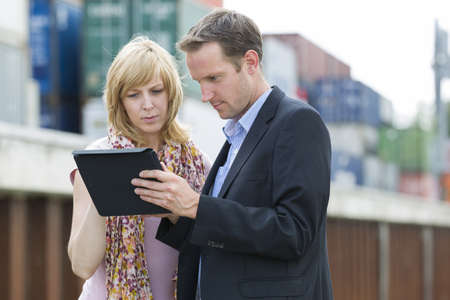 Business people using digital tablet outdoors