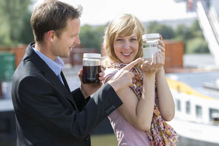 Colleagues with clean and dirty water containers from sewage treatment plant Stock Photo