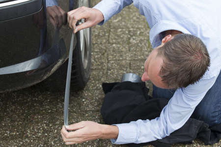 Mid adult man using duct tape to fix his car  Horizontal shot