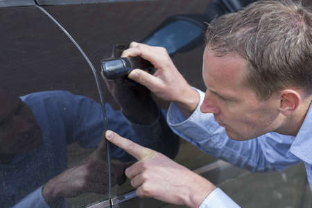 scratched metal: Mid adult man checking his car for scratches and dents  Horizontal shot