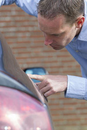scratched metal: Mid adult man checking his car for scratches and dents  Vertical shot