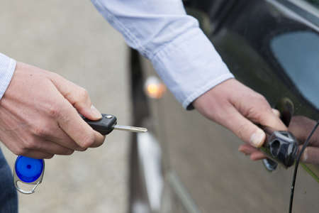 Cropped view of man with key unlocking car door  Horizontal shot  Standard-Bild