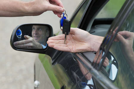 side keys: Mid adult man receiving key of his new car  Horizontal shot