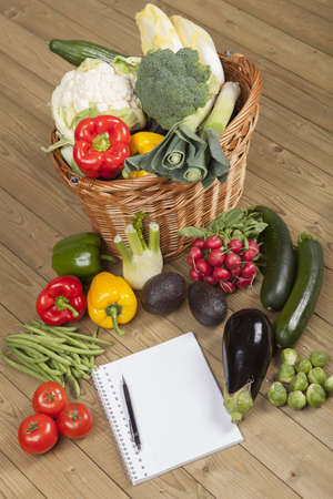 Open notebook ready for writing recipe with vegetables and basket on wooden surface