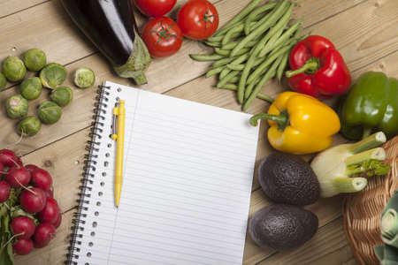 avacado: High angle view of vegetables with book and pen on wooden surface