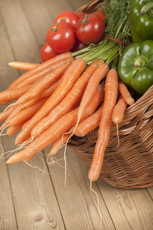 Basket full of carrots, capsicum and tomatoes on wooden surface