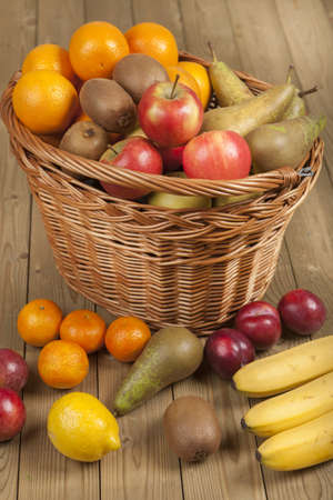 Healthy and fresh fruits and basket on wooden surface