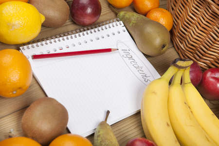 Book and pencil admist variety of fruits on wooden plank