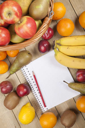 Cropped image of fruits in basket with pencil and book on wooden surface Stock Photo