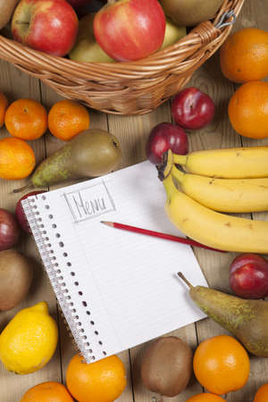 Cropped image of various fruits in basket with pencil and book on wooden surface Stock Photo