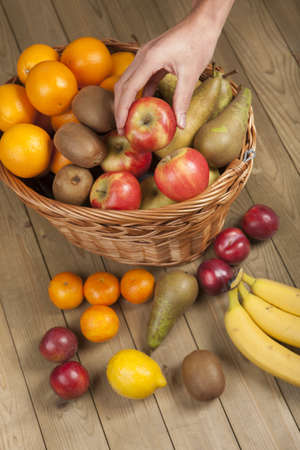 hand basket: Cropped image of hand picking up an apple from basket full of fruits on wooden surface