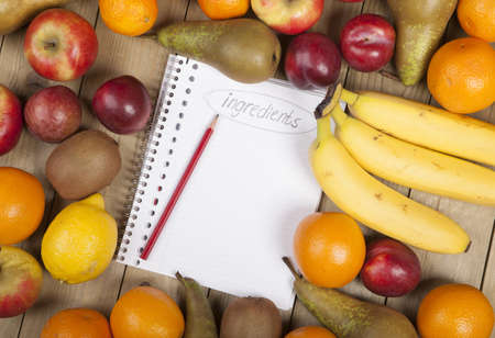 Pencil on book admist variety of fruits on wooden plank