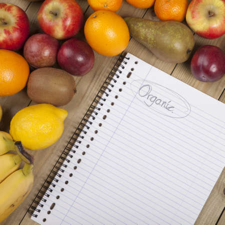 Organic fruits and book on wooden surface Stock Photo