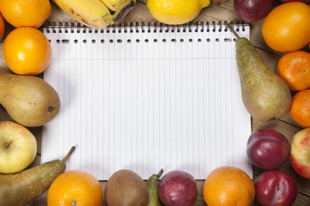 Spiral book admist variety of fruits on wooden plank