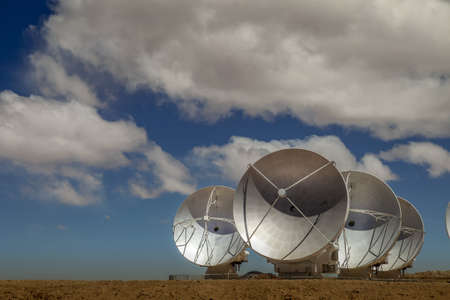 Four satellite dishes out of 60 of ESOs ALMA array pointed to the side Stock Photo