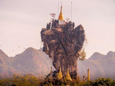Kyaut Ka Latt Pagoda perched atop a rock cliff in a lake, Hpa An, Myanmar. Фото со стока