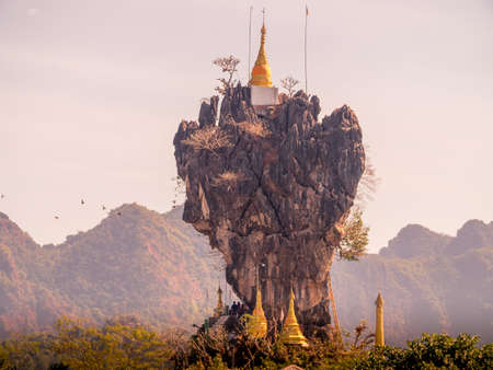 Kyaut Ka Latt Pagoda perched atop a rock cliff in a lake, Hpa An, Myanmar. Stockfoto
