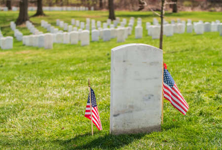 Tombstone at Arlington National Cemetery with US flags