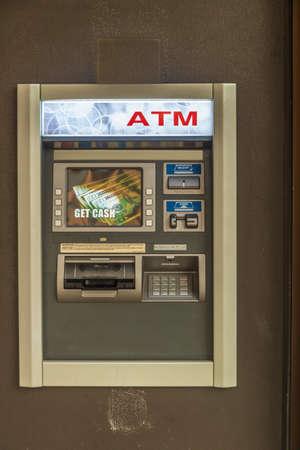 Generic ATM machine a brown wall Banco de Imagens