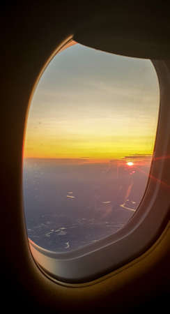 Widok z lotu ptaka z okna samolotu z pięknym zachodem słońca na niebie