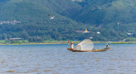 Gull flying in front of a Fisherman at Inle Lake