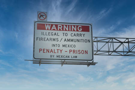 Warning sign above road urging travelers not to carry firearms and ammunition across the border from the U.S. to Mexico