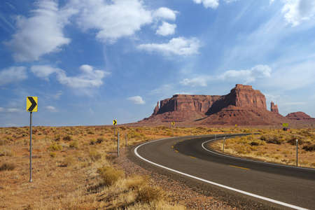 Highway in Monument Valley, Utah, USA - road curve leading towards the hills.